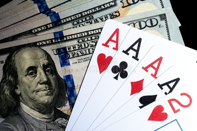 Quatro cartões de jogo dos ás e pilhas de 100 dólares de contas americanos foto de stock royalty free