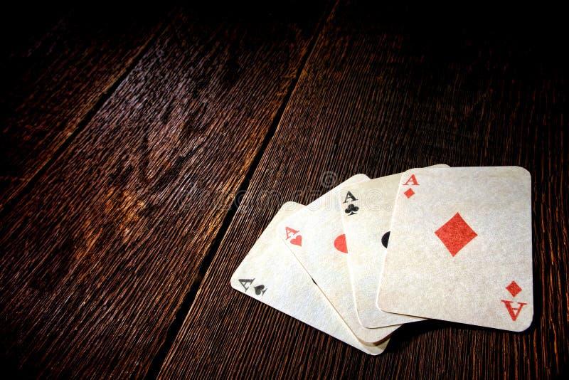 Quatro cartões do pôquer do vintage dos áss na tabela velha do bar imagens de stock