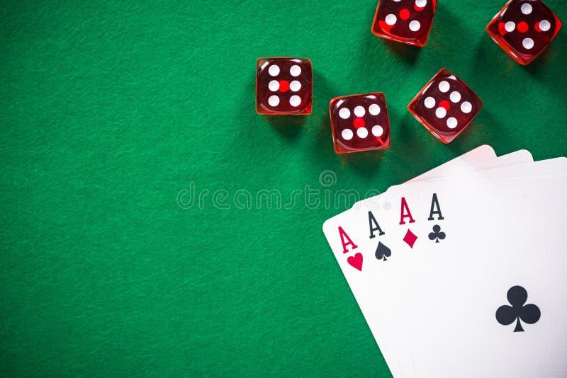 Quatro cartões e vermelhos do pôquer dos ás cortam na tabela do casino imagem de stock