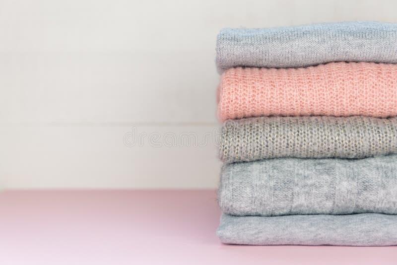 Quatro cinzentos e as ligações em ponte uma feitas malha dobradas cor-de-rosa que colocam no rosa pastel surgem Conceito mínimo o fotografia de stock