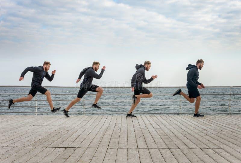 Quatro clone dos homens que correm nos esportes vestem ao longo do beira-mar imagens de stock royalty free