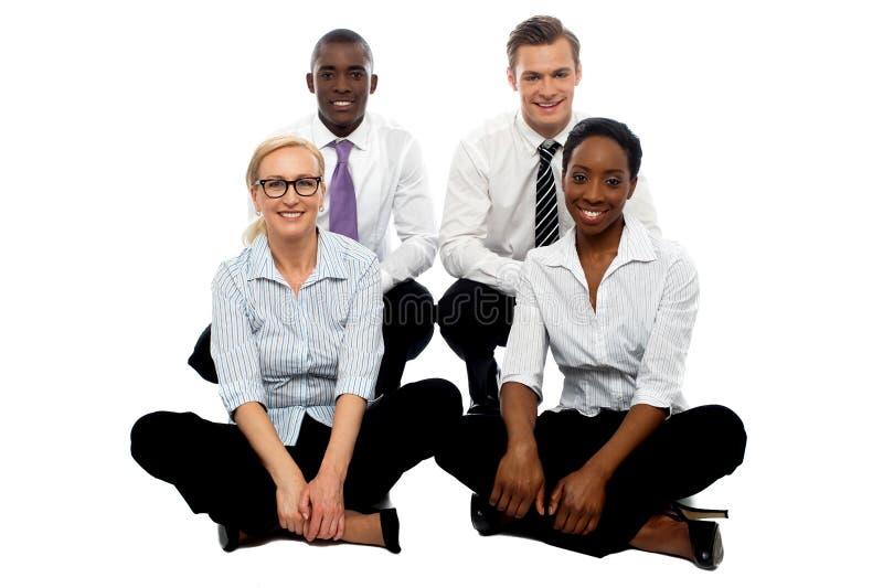 Quatro colegas do negócio que sentam-se no assoalho fotos de stock royalty free