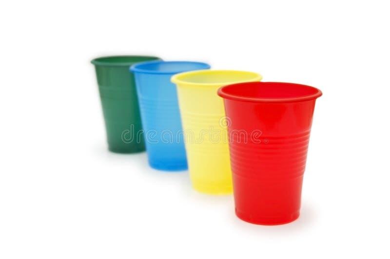 Quatro copos plásticos coloridos imagem de stock