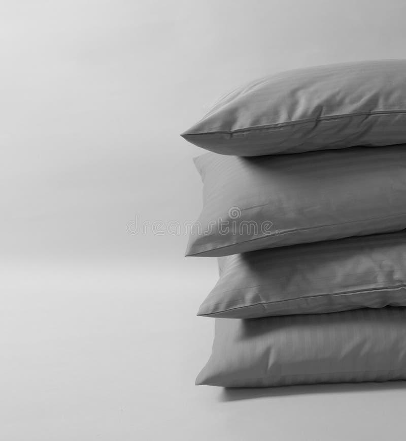 Quatro coxins empilhados contra o fundo branco Descansos cinzentos no fundo branco imagens de stock royalty free