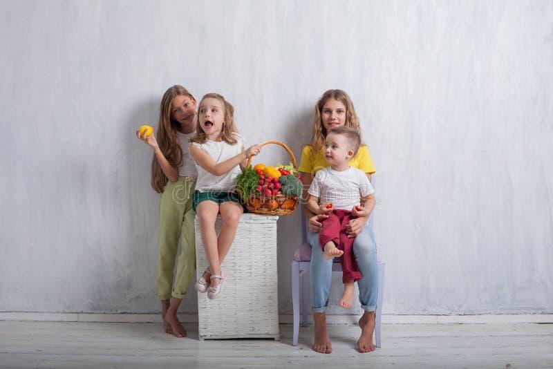 Quatro crianças com alimento saudável dos legumes frescos fotos de stock royalty free
