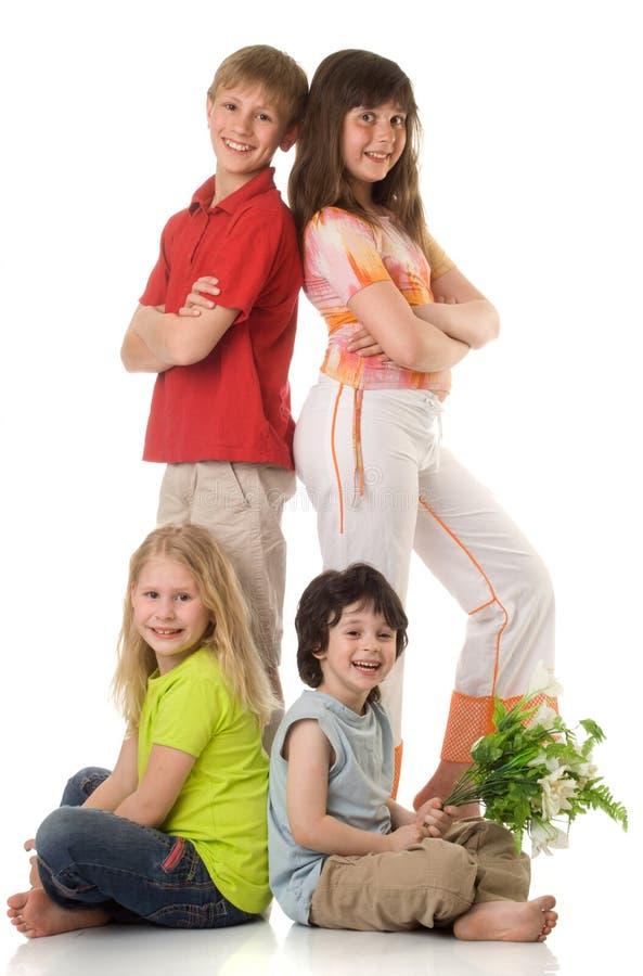 Quatro crianças com flores fotografia de stock