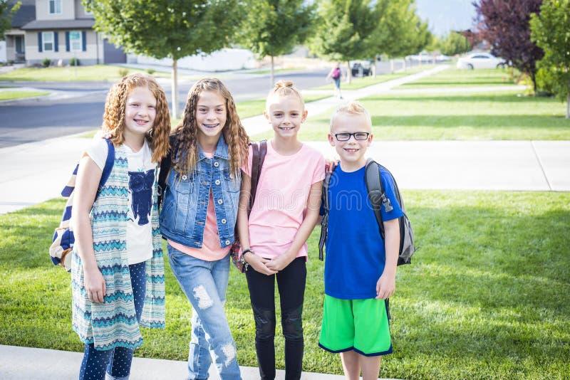 Quatro crianças da escola que dirigem fora à escola na manhã foto de stock