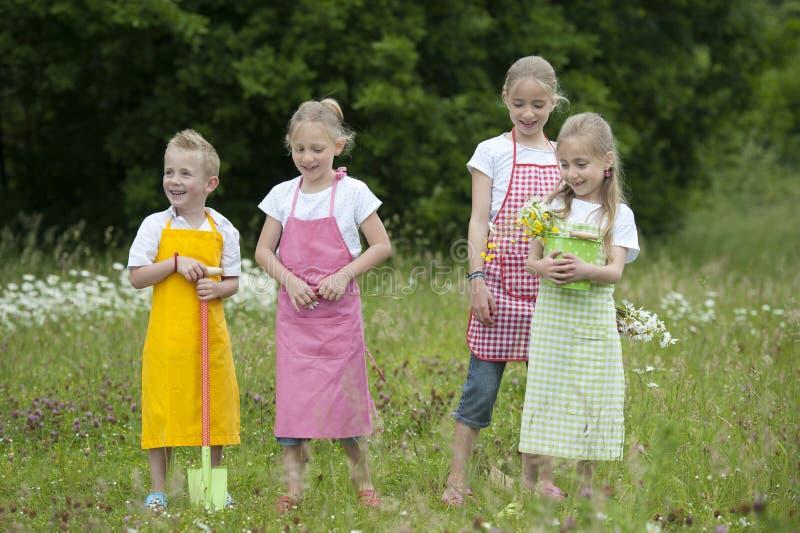 Quatro crianças de jardinagem com aventais imagem de stock