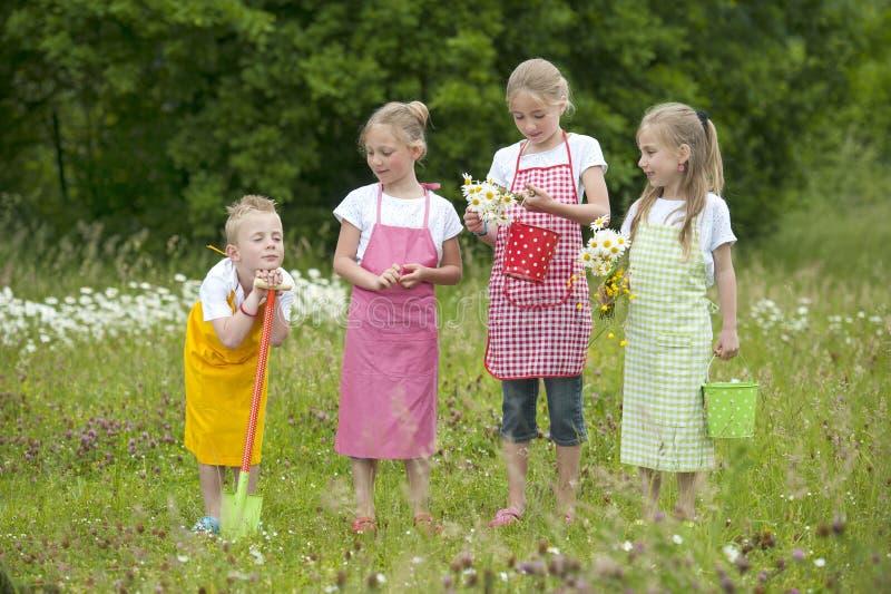 Quatro crianças de jardinagem com aventais fotografia de stock