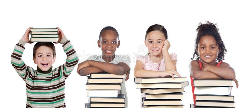 Quatro crianças engraçadas com muitos livros fotos de stock