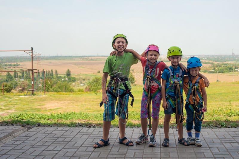 Quatro crianças estão vestindo capacetes e a roupa de escalada e estão prontas para superar obstáculos em um parque extremo imagem de stock
