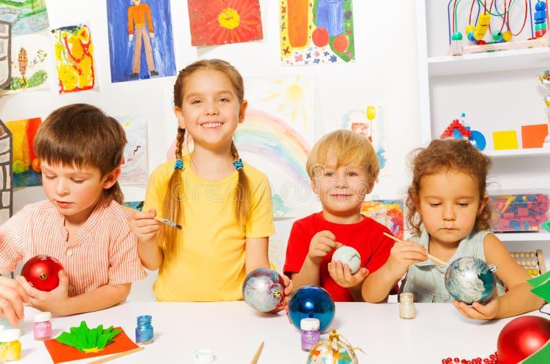 Quatro crianças pintam bolas do ano novo para a árvore do Xmas foto de stock royalty free