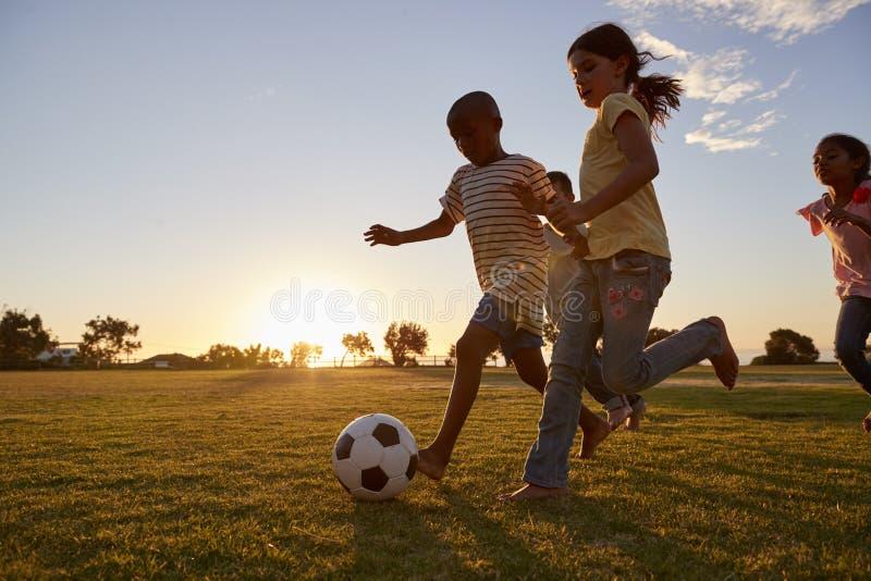 Quatro crianças que competem após um futebol que exerce em um campo fotos de stock