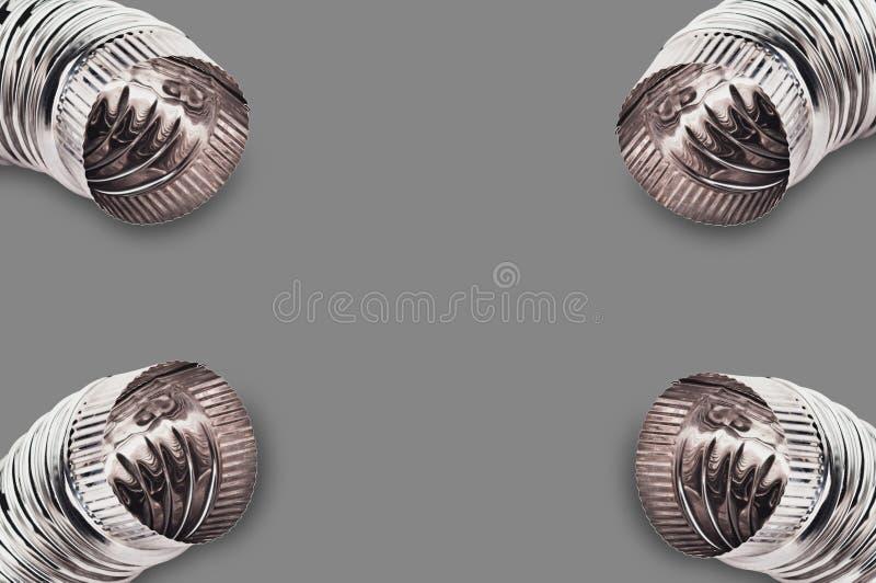 Quatro cromam cotovelos ondulados das tubulações para o ar, a água, o óleo ou o gás nos cantos no fundo cinzento imagem de stock