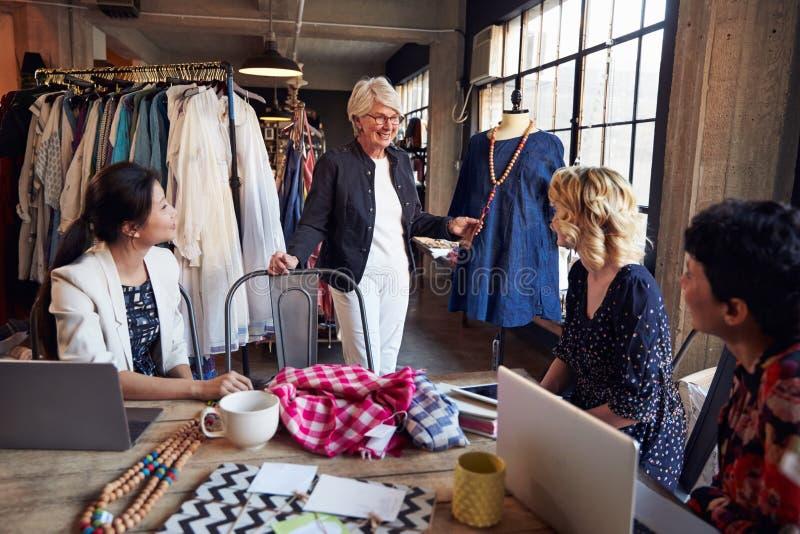 Quatro desenhadores de moda na reunião que discutem o vestuário foto de stock royalty free