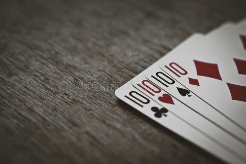 Quatro dez em uma tabela de madeira conceito do jogo e do lugar para seu texto Pás reais do flash do casino dos cartões de jogo fotos de stock