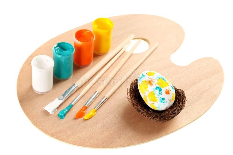 Quatro escovas de pintura da arte com pintura acrílica poli nas cores azuis brancas, amarelas, da laranja e do aqua e no ovo deco fotografia de stock