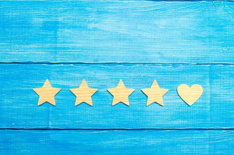 Quatro estrelas e um coração em um fundo azul Seleção do usuário e dos clientes Reconhecimento e admiração universais Avaliação d fotografia de stock royalty free