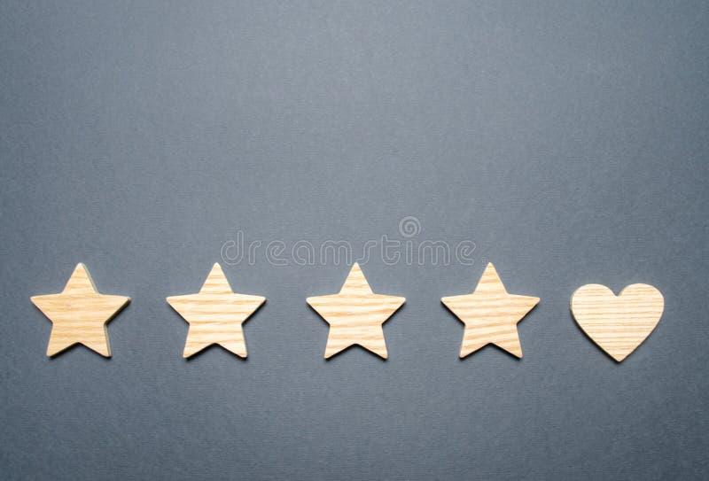 Quatro estrelas e um coração em vez do quinto O conceito da escolha do cliente Reconhecimento geral do de alta qualidade e bom imagens de stock royalty free