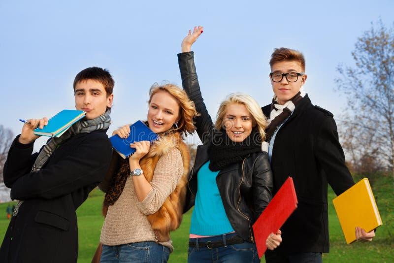 Quatro estudantes com cheering dos livros foto de stock royalty free