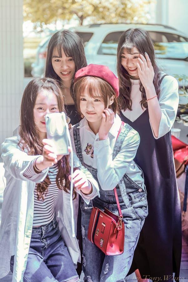 Quatro estudantes fêmeas entusiasmado sobre o auto-temporizador fotografia de stock