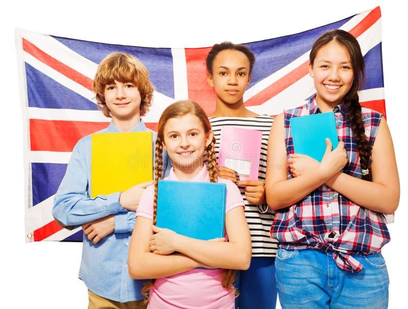 Quatro estudantes felizes que estão contra a bandeira britânica fotografia de stock