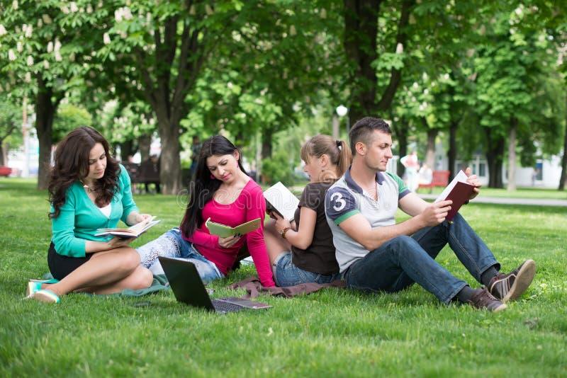 Quatro estudantes universitário que comparam suas notas imagens de stock royalty free