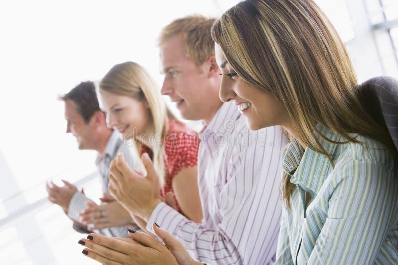 Quatro executivos que aplaudem dentro o sorriso imagem de stock royalty free