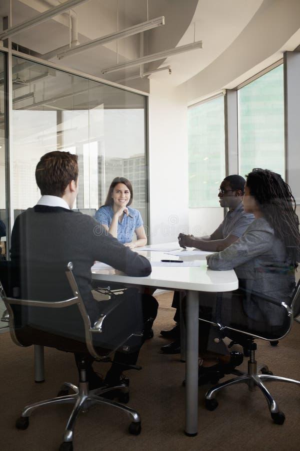 Quatro executivos que sentam-se em uma tabela de conferência e que discutem durante uma reunião de negócios imagem de stock