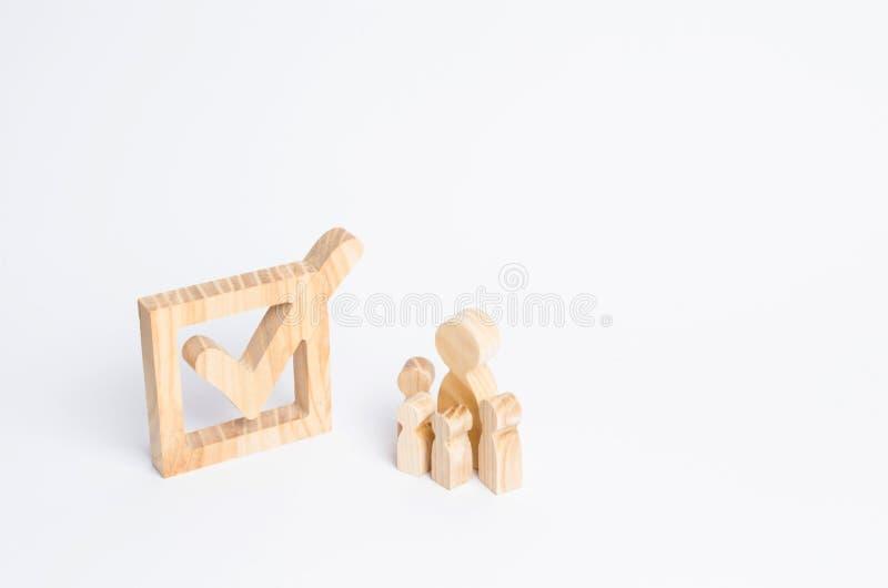 Quatro figuras humanas de madeira estão junto ao lado de um tiquetaque na caixa O conceito das eleições e de tecnologias sociais  fotos de stock royalty free