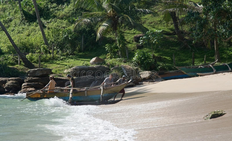 Quatro homens arrastam seu barco de madeira pequeno fotos de stock