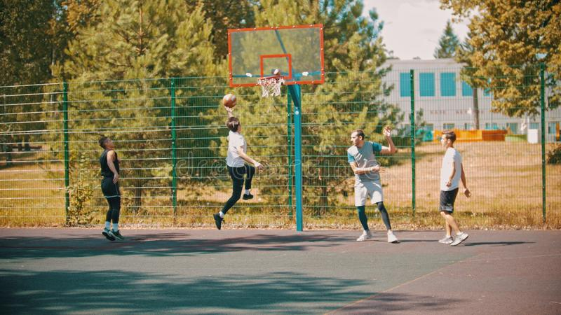 Quatro homens novos que jogam o basquetebol no ar livre da terra de esportes imagens de stock royalty free