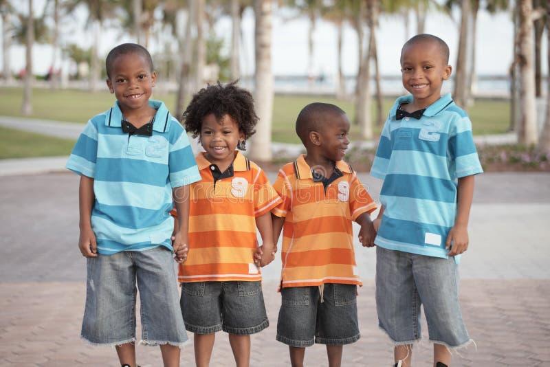 Quatro irmãos que prendem as mãos fotografia de stock