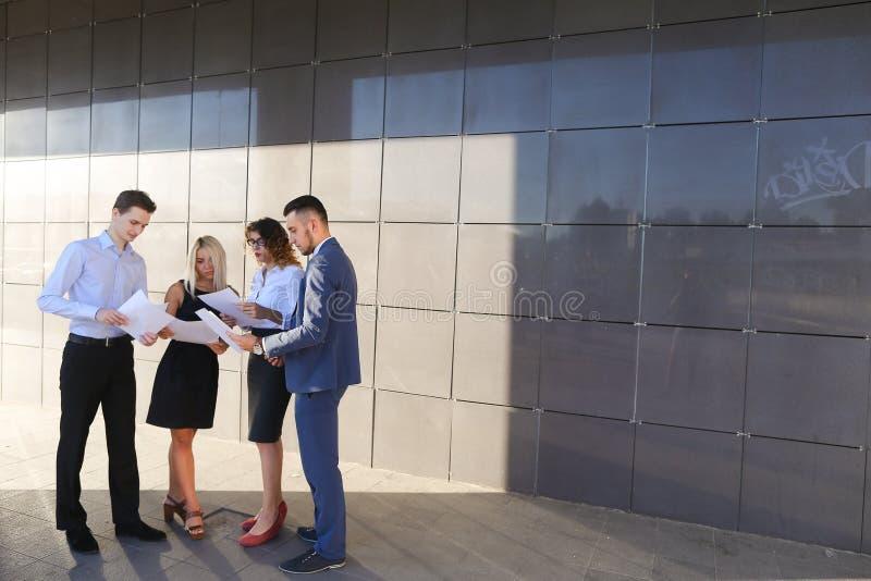 Quatro jovens, dois homens e duas mulheres, estudantes, comunicam-se, fotos de stock