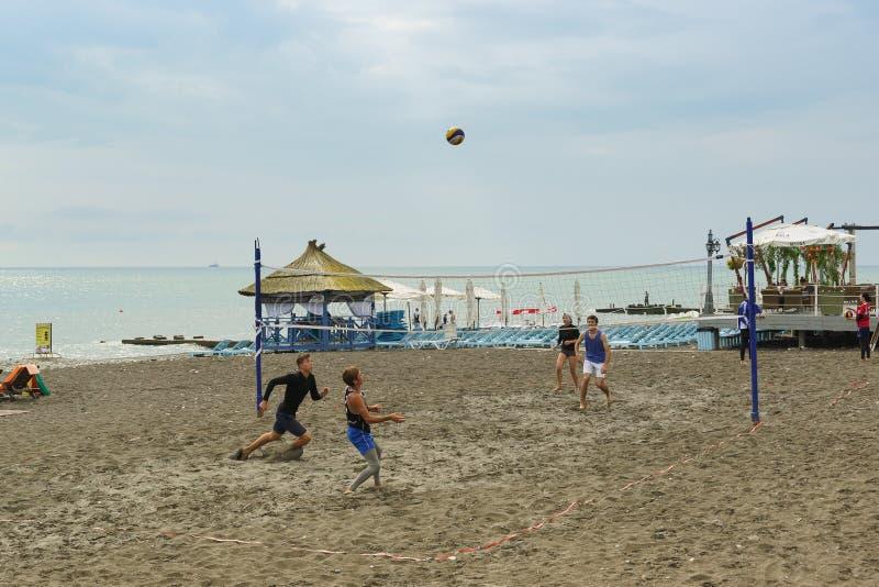 Quatro jovens jogam entusiasticamente o voleibol de praia na costa do Mar Negro fotografia de stock royalty free