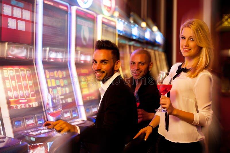 Quatro jovens que jogam slots machines no casino imagens de stock