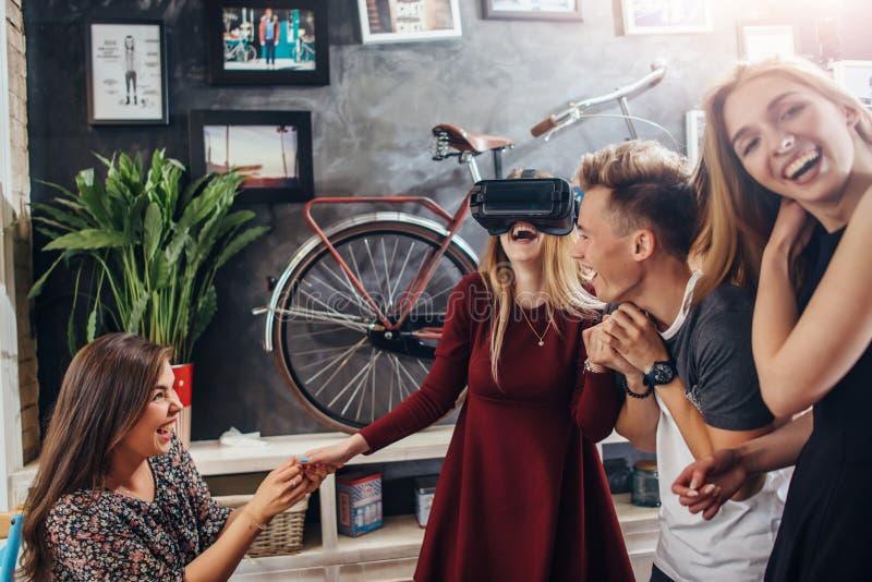 Quatro jovens que têm uma nova tecnologia dos testes do partido dos vidros da realidade virtual da visão 3d que jogam jogos inter foto de stock