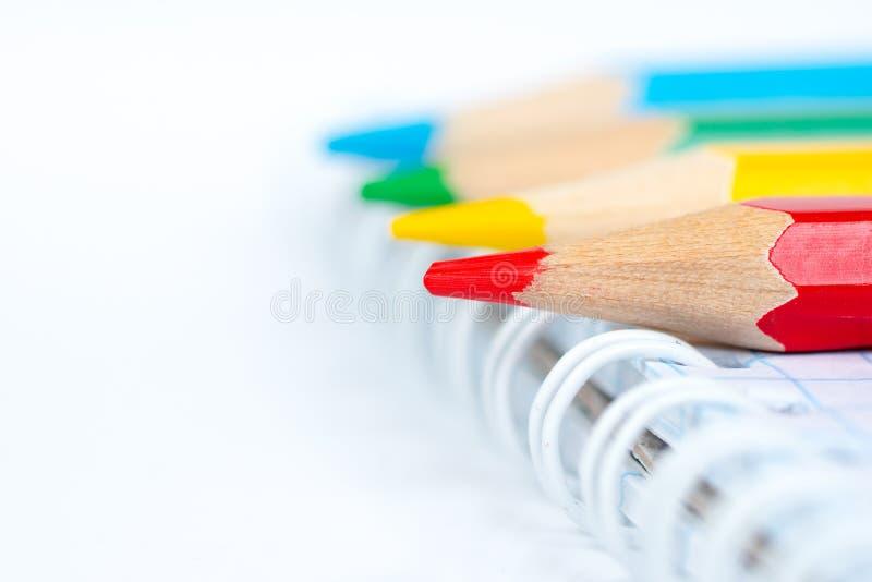 Quatro lápis coloridos com bloco de notas imagem de stock
