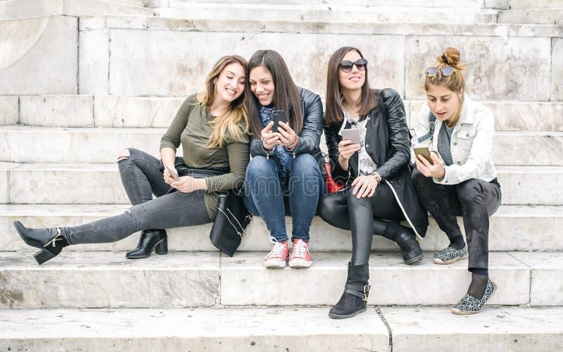 Quatro meios sociais de observação felizes do Internet das namoradas no smartp foto de stock