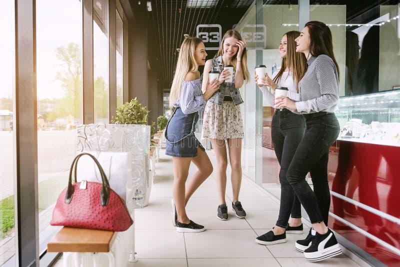 Quatro meninas de compra falam e riem, na alameda imagens de stock royalty free