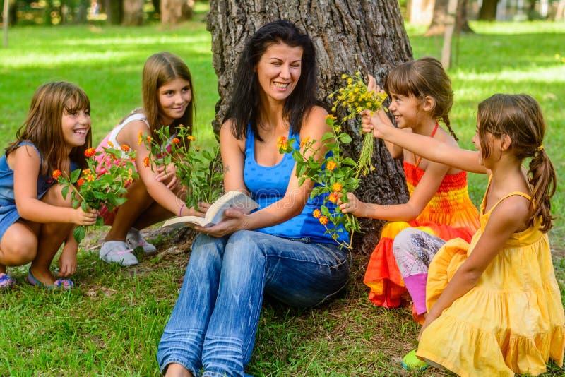 Quatro meninas que dão flores do mum no parque foto de stock royalty free