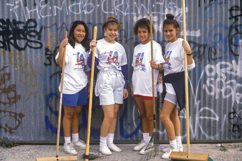 Quatro meninas que participam na limpeza da comunidade fotografia de stock