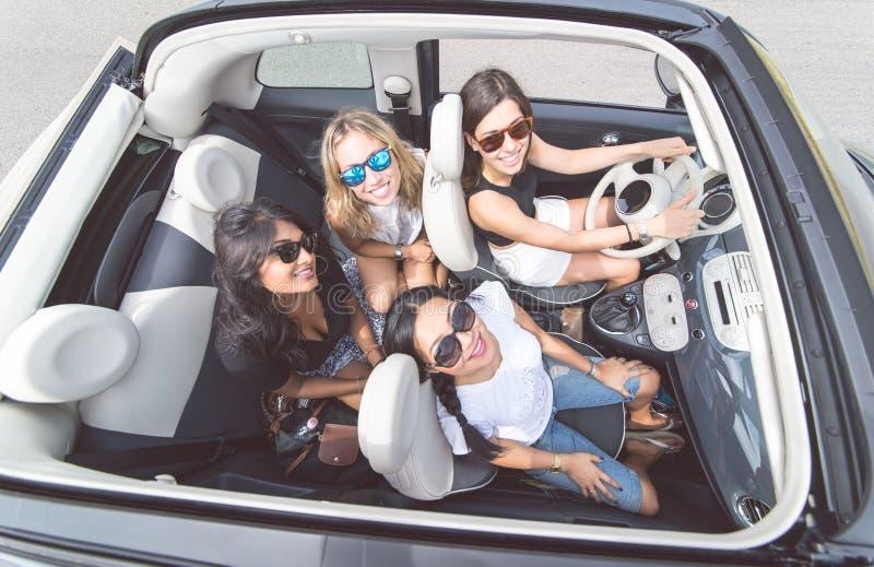 Quatro meninas que têm o divertimento em um carro convertível fotografia de stock royalty free