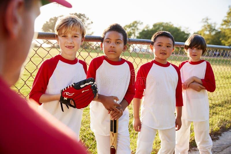 Quatro meninos em uma equipa de beisebol que escuta o treinador, fim acima fotografia de stock