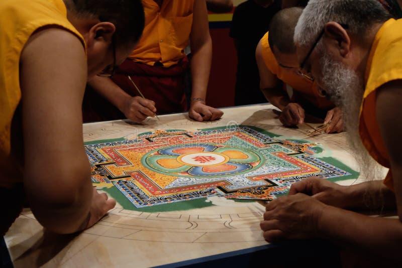 Quatro monges que trabalham na mandala foto de stock royalty free