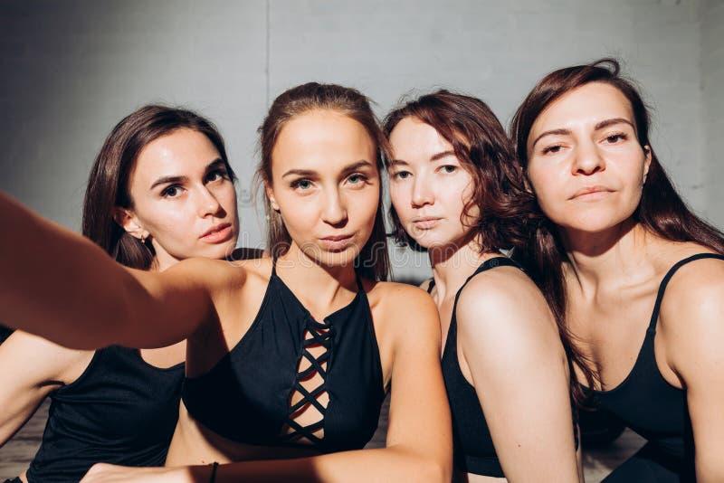 Quatro mulheres agradáveis que levantam à câmera fotos de stock royalty free