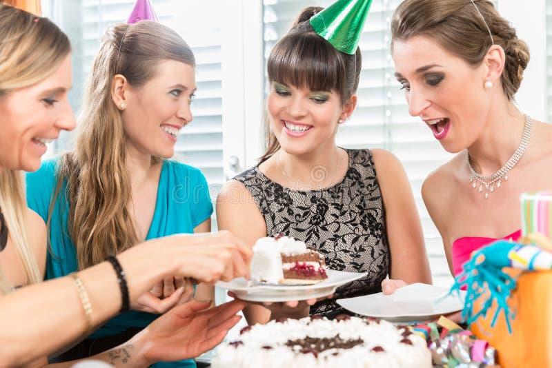 Quatro mulheres e melhores amigos bonitos que sorriem ao compartilhar de um bolo de aniversário fotos de stock royalty free