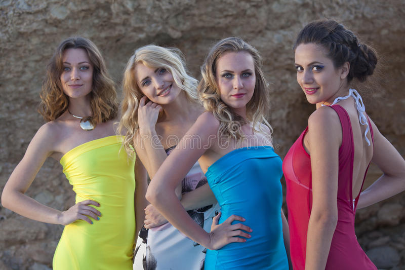 Quatro mulheres em vestidos do verão imagens de stock