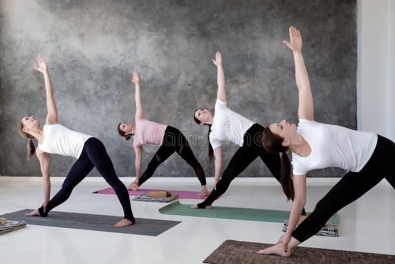 Quatro mulheres europeias que praticam a ioga, pose de Trikonasana foto de stock royalty free