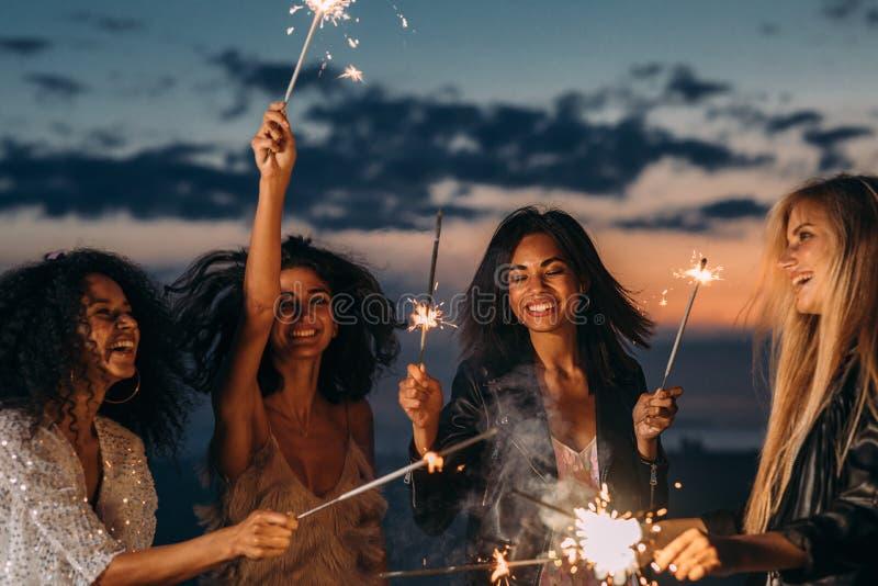 Quatro mulheres felizes celebrando ao sol foto de stock royalty free
